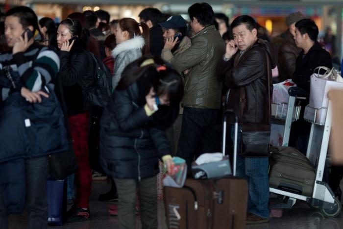 Пассажиры в ожидании посадки на самолёт. 6 февраля 2013 года, Международный аэропорт Пекина. Фото: Ed Jones/AFP/Getty Images