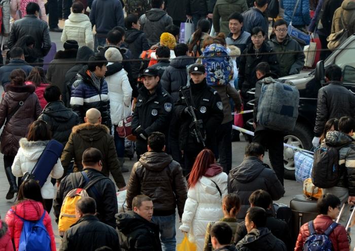 Полицейские смешались с толпой людей. 26 января 2013 года, железнодорожный вокзал Пекина. Фото: MARK RALSTON/AFP/Getty Images