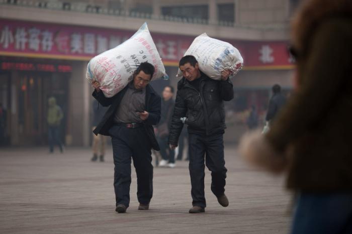 Люди с большими баулами едут домой. 27 января 2013 года. Фото: Ed Jones/AFP/Getty Images
