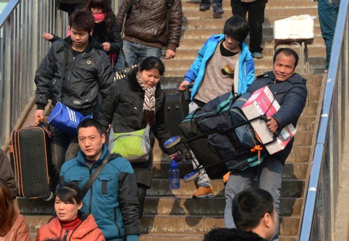 Люди с большми сумками спускаются по лестнице. 26 января 2013 года, Пекин. Фото: MARK RALSTON/AFP/Getty Images
