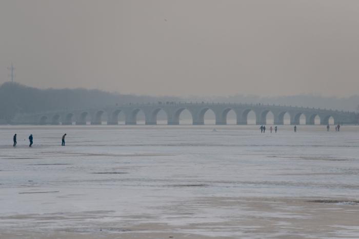 27 декабря 2012 года в Пекине. Люди, идущие по замерзшему озеру. Фото: Ed Jones/AFP/Getty Images