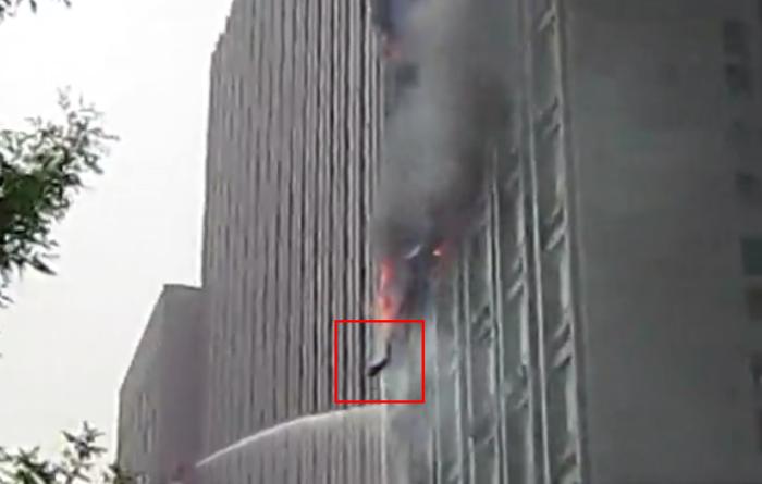 Пожар офисного здания в Тяньцзине 4 марта, кадр из видео. Видно, как в чёрном дыму из окна кто-то выпрыгнул.  Фото с epochtimes.com