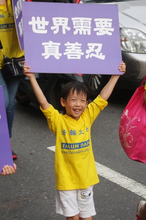 Надпись на плакате у мальчика: «Мир нуждается в истине, доброте, терпении». Тайбэй, Тайвань. Июль 2013 года. Фото: The Epoch Times