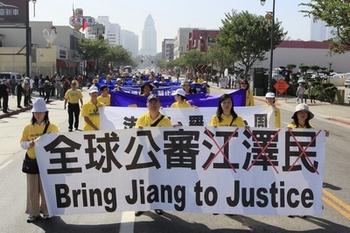 Последователи Фалуньгун несут плакат с призывом отдать под суд зачинщика репрессий Цзян Цзэминя. Лос-Анджелес, США. Октябрь 2013 года. Фото: The Epoch Times