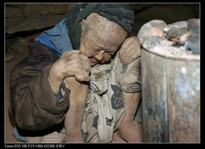 У бабушки Ван, которой уже за 80 лет, нет денег на лечение. Она часто подолгу сидит так, прислонившись к тёплой печи, чтобы хоть немного ослабить свои страдания. Провинция Гуйчжоу. Фото с epochtimes.com