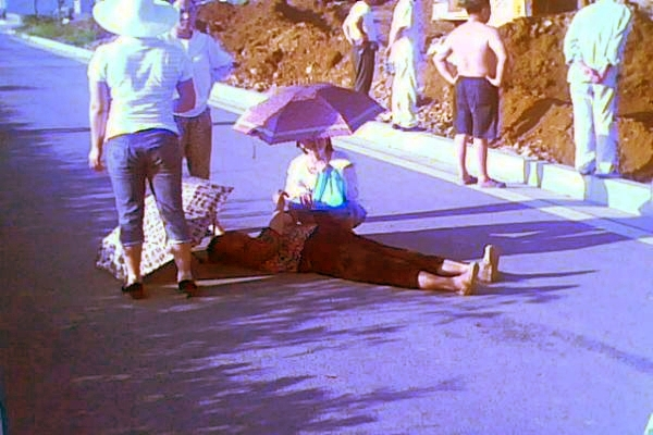 От удара чиновника ногой женщина потеряла сознание. Чиновники продолжают руководить работами по сносу. Провинция Хунань. Июль 2013 года. Фото с epochtimes.com