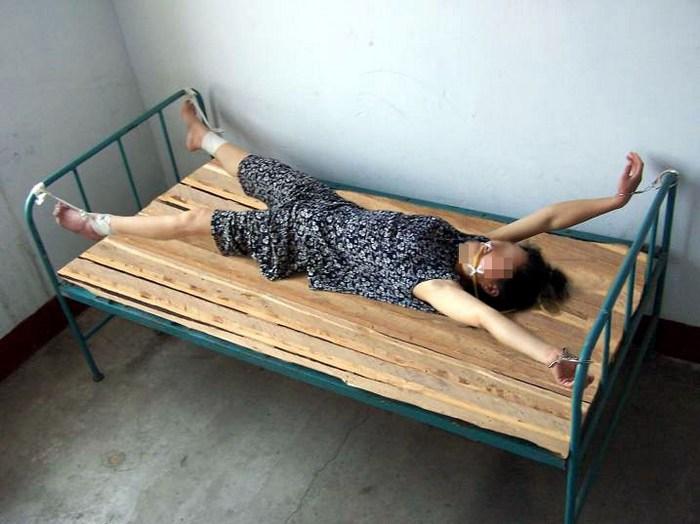 Инсценировка одной из десятков видов пыток — «кровать мертвеца», применяемых в китайских тюрьмах и лагерях к сторонникам Фалуньгун, в том числе и к пожилым людям. Фото: minghui.org
