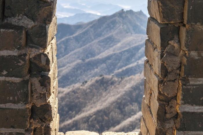 Вид через окно сторожевой башни Великой китайской стены. Как только отважные солдаты получают срочные сообщения о вражеском нападении, они тут же бросаются на защиту своей страны и полны решимости выполнить свой гражданский долг без всяких колебаний. Фото: Mirko Kirstein / Photos.com
