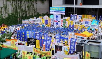 Участники парада в Гонконге собрались у здания администрации на митинг. Внизу одетые в зелёные рубашки члены «Ассоциации содействия молодёжи Гонконга» пытаются заглушить выступающих криками и звукоусиливающей аппаратурой. Фото: Song Xianglong/Epoch Times