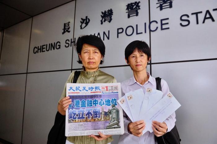 Два сотрудника китайского языка издания Epoch Times в Гонконге стоят возле полицейского участка, куда они 12 сентября пожаловались на враждебную кампанию против газеты. Женщина слева держит газету, а женщина справа держит письма для рекламодателей, которые должны были дискредитировать издание. Фото: Song Xianglong/Epoch Times