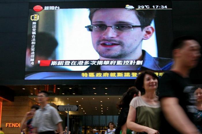 На экране репортаж об Эдварде Сноудене, бывшем сотруднике ЦРУ, который вывез сверхсекретные документы об американских программах наблюдения, торговый центр Гонконга, 23 июня 2013 года. Фото: AP Photo/Vincent Yu
