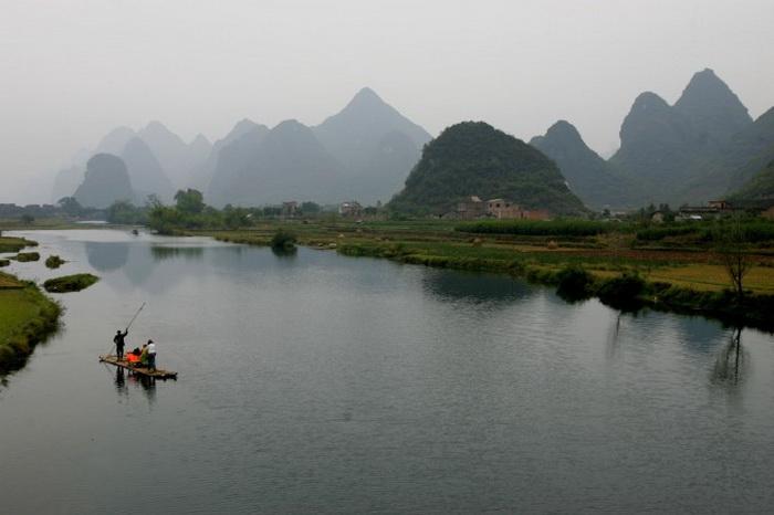 Округ Яншо, Китай. Крестьянин управляет бамбуковым плотом, катая туристов по реке Лицзян в округе Яншо, недалеко от Гуйлиня, в Гуанси-Чжуанском автономном районе, 19 ноября 2006 г. Гуйлинь — город, название которого произошло от названия его лавровых лесов, известен своим прекрасным видом карстовых гор, часто изображаемых китайскими пейзажистами. Гуйлинь является родиной для более десяти групп этнических меньшинств, и его посещают свыше 12 миллионов туристов ежегодно. Фото: China Photos/Getty Images