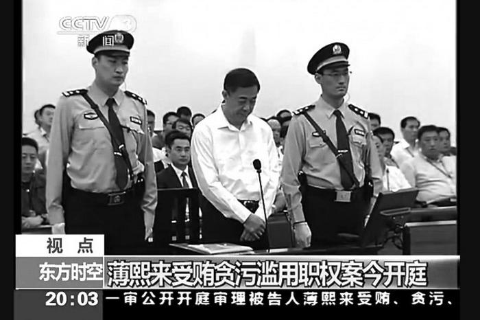 Бывший член Политбюро Бо Силай стоит между двумя охранниками в зале суда города Цзинань провинции Шаньдун, 22 августа. Основная задача суда над Бо Силаем состояла в том, чтобы не нарушить баланс сил в Китае. Фото с сайта theepochtimes.com