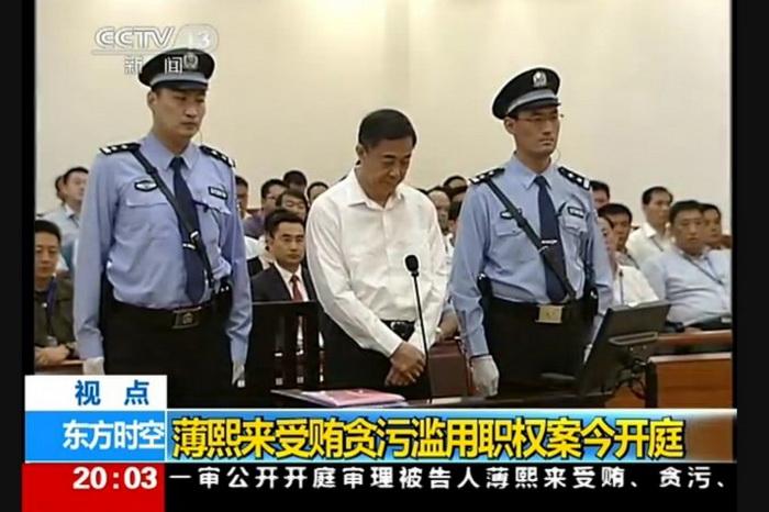 Бывший член Политбюро Бо Силай стоит между двумя охранниками в суде города Цзинань провинции Шаньдун в первый день суда, 22 августа. Фото с сайта www.theepochtimes.com