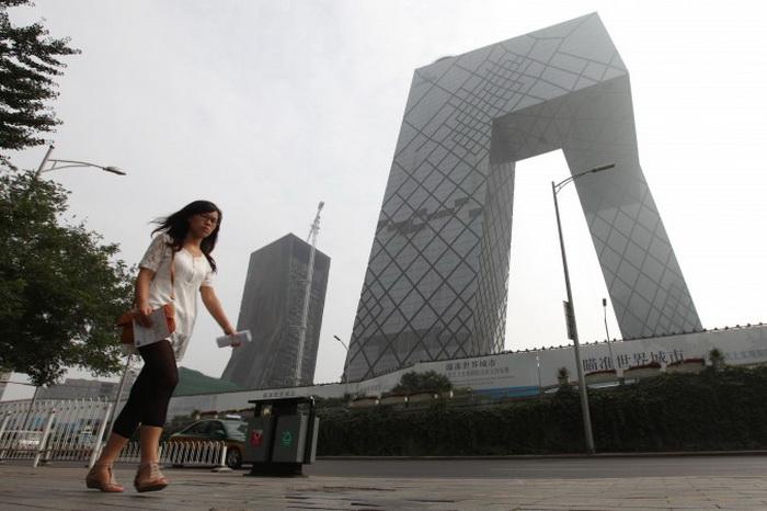 Женщина проходит мимо здания Центрального телевидения Китая (CCTV, China Central Television), Пекин, 13 августа 2010 года. Продюсер CCTV Ван Цинлэй был вынужден уйти в отставку после того, как он раскритиковал нападки СМИ на известных блогеров. Фото: Franko Lee/AFP/Getty Images