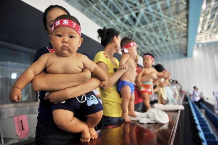 Всё большее число богатых китайцев пользуются услугами американских суррогатных матерей, чтобы обойти политику одного ребёнка в Китае. На фото китайские младенцы с родителями готовятся к конкурсу детского плавания. Фото: STR/Getty Images