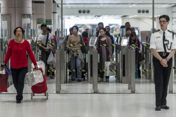 Люди пересекают границу между материковым Китаем и Гонконгом 1 марта 2013 года. Новые правила получения визы, которые вступят в силу с 1 сентября 2013 года, сделают переход из Гонконга на материк менее удобным для иностранных бизнесменов. Фото: Philippe Lopez/AFP/Getty Images