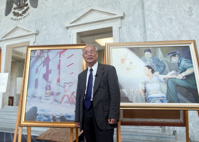 Профессор Чжан Куньлунь возле своей картины «Красная стена», которая передаёт его опыт как узника совести в Китае. Фото: XIMING/EPOCH TIMES