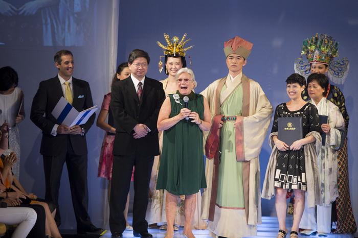 Американский дизайнер театральных костюмов Энн Рот (в зелёном) вручает Золотой приз со словами, что не видела другой такой показ мод, который бы «сочетал безмятежность с эмоциональной выразительностью». Фото: NTD Television