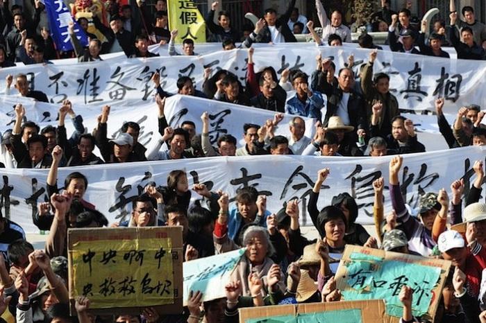 Крестьяне держат баннеры во время акции протеста в деревне Укань провинции Гуандун 19 декабря 2011 г., требуя, чтобы центральные власти приняли меры против незаконного захвата земли, и смертной казни местного руководителя, находившегося под арестом. Застройщики, действующие вместе с местными чиновниками, чтобы отобрать землю и дома людей с небольшой компенсацией или без неё, находятся среди наиболее презираемых людей в Китае. Фото: STR/AFP/Getty Images