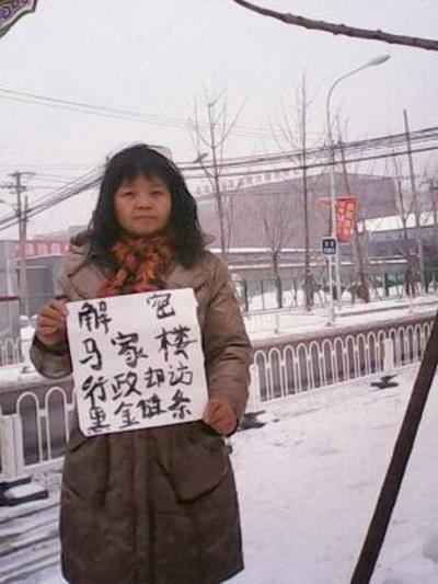 8 февраля четыре апеллянта стоят на улицах Пекина, держа в руках плакаты, призывающих китайскую компартию «раскрыть тайны фондов безопасности Мацзялоу». Фото: Human Rights Campaign in China