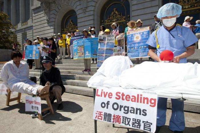 Актёры имитируют методы пыток, применяемых к последователям Фалуньгун в Китае, в то время как демонстранты держат плакаты. Сан-Франциско, 5 сентября. Фото: Epoch Times