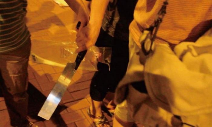 Этим большим ножом вскоре будут запугивать журналиста телевидения New Tang Dynasty, который вёл репортажи с акций последователей Фалуньгун в Гонконге, 4 июля 2012 года. Фото: Epoch Times