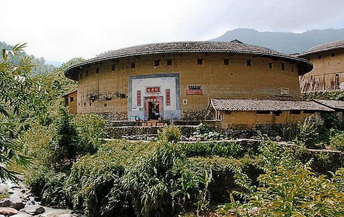 Их стены высотой 33-56 футов и толщиной 6,5 фута сделаны из утрамбованной земли и армированы бамбуковыми прутьями. У каждого Тулоу есть только один вход на уровне земли. У большинства жилищ окна обычно маленькие и находятся на третьем этаже. Фото: Xiao Yue