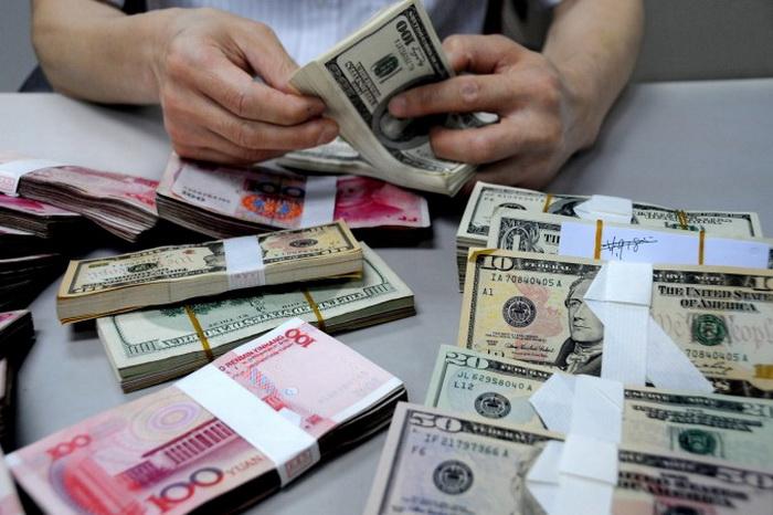 Сотрудник считает деньги в отделении Банка Китая, 10 августа 2011 года. Хотя Китай в государственных средствах массовой информации в последнее время утверждает, что иностранная валюта течёт в Китай, за последние три года эта тенденция была обратной. Фото: ChinaFotoPress/Getty Images