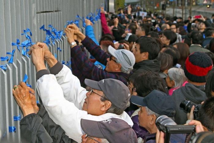 После акции люди повязали синие ленты на ограде снаружи офиса администрации Лян Чжэньина. Фото: Epoch Times