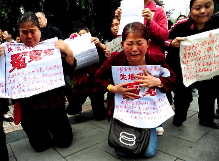 Женщины-просительницы стоят на коленях около здания суда в Чунцине 13 мая 2010 года. На плакатах слова, осуждающие правительственных чиновников, отобравших их земли и имущество. Фото: AFP/AFP/Getty Images