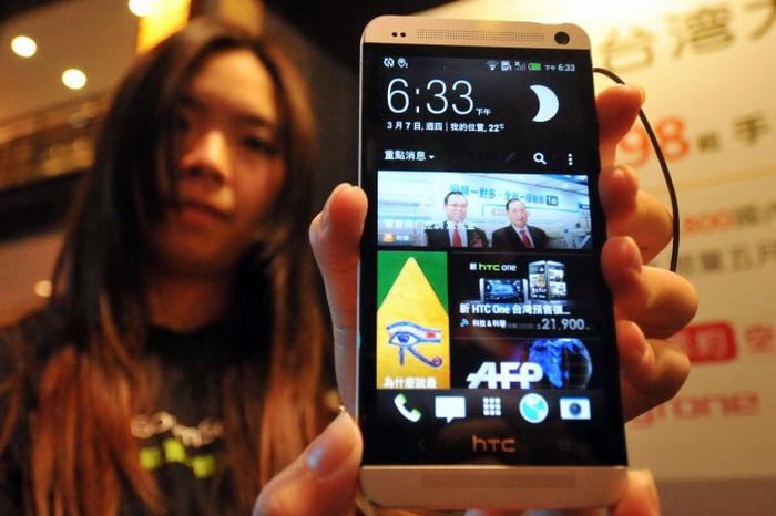 Девушка с новым смартфоном HTC, Тайбэй, 7 марта 2013 года. Фото: Mandy Cheng/AFP/Getty Images