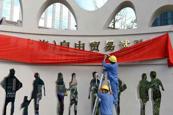 Рабочие украшают ворота в зону свободной торговли в Шанхае, 23 сентября 2013 года. Фото: STR/AFP/Getty Images