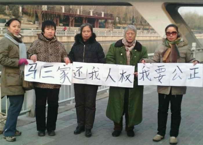Бывшие узницы женского трудового лагеря Масанцзя 16 декабря поехали в Пекин. Они держат плакат с надписью «Масанцзя, верни мои права, я хочу справедливости». Фото: Human Rights Campaign in China
