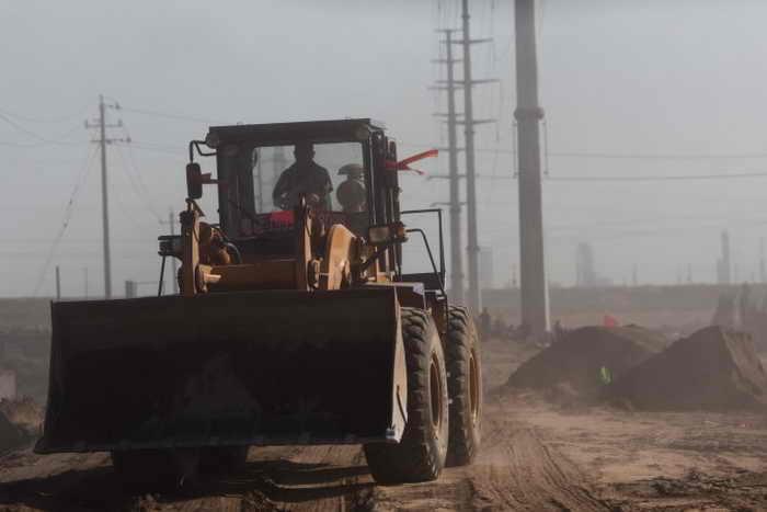 Фронтальный погрузчик возле «токсичных озёр» в окружении перерабатывающих редкие земли предприятий вблизи города Баотоу, Внутренняя Монголия, 19 августа 2012 года. Китай усилил горнодобывающую промышленность шестью государственными компаниями. Фото: Эд Джонс/AFP/Getty Images
