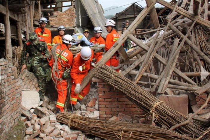 Спасатели выносят парализованного пожилого человека из разрушенного дома в г. Цинжэнь уезда Лушань, провинция Сычуань, где 20 апреля 2013 г. произошло землетрясение магнитудой 7. Фото: AFP/Getty Images