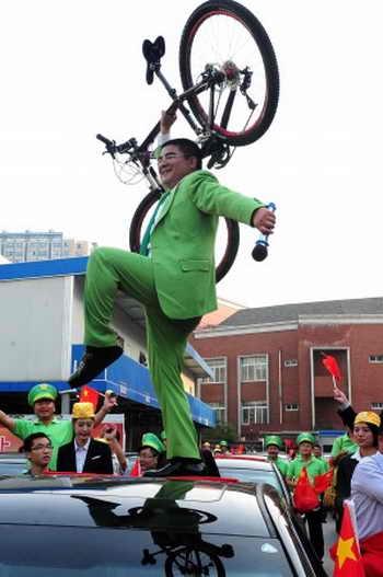 Китайский филантроп Чэнь Гуанбяо держит велосипед на крыше нового автомобиля, 10 октября 2012 года, Пекин. Он подарил новые «легковушки» 43 владельцам японских автомобилей, которые были повреждены месяцем ранее, во время общенациональных протестов против Японии. Фото: STR/AFP/GettyImages