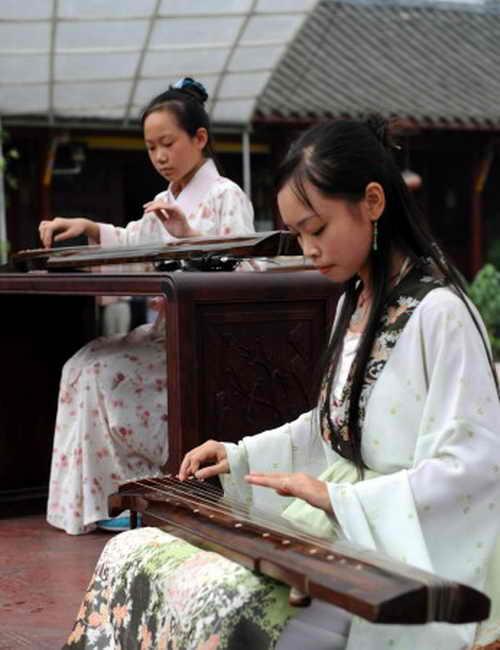 Девушки играют на цине — китайском классическом музыкальном инструменте. China Photos/Getty Images