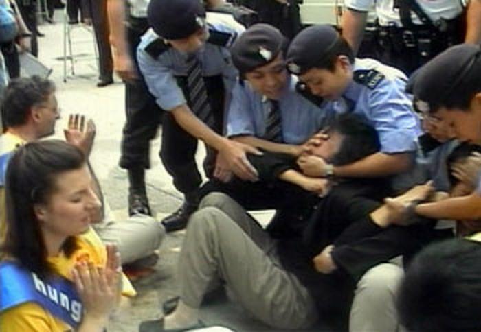 Группа последователей Фалуньгун проводит сидячую акцию протеста перед зданием китайского Бюро по связям 14 марта 2002 года. Все 16 участников были арестованы за создание помех в общественном месте. Последователи Фалуньгун обратились в Высший апелляционный суд, который отменил все обвинения в мае 2005 года. Фото: Epoch Times