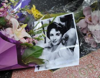 Поклонники возложили цветы о фотографии на звезду Элизабет Тейлор. Фото: MARK RALSTON/AFP/Getty Images