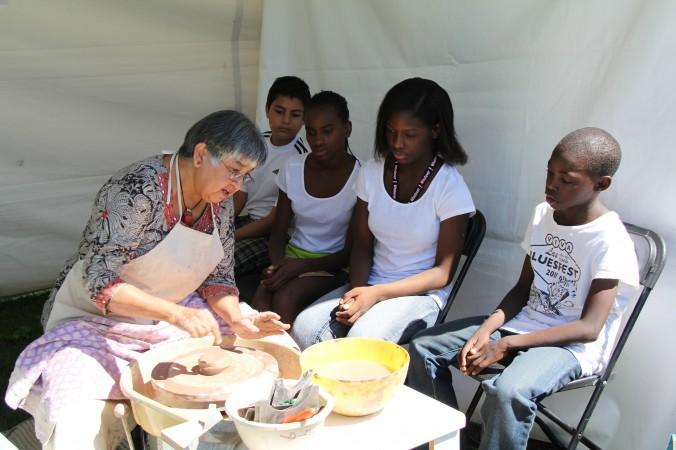 Дети, наблюдая за изготовлением глиняной посуды, попытались поучаствовать в процессе. Фото: Pam McLennan/ Epoch Times