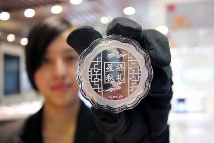 Продавщица показывает серебряную монету в магазине города Чжоукоу провинции Хэнань, 29 августа 2013 года. Монеты из золота и серебра стали  популярными у богачей Китая. Фото: STR/AFP/Getty Images