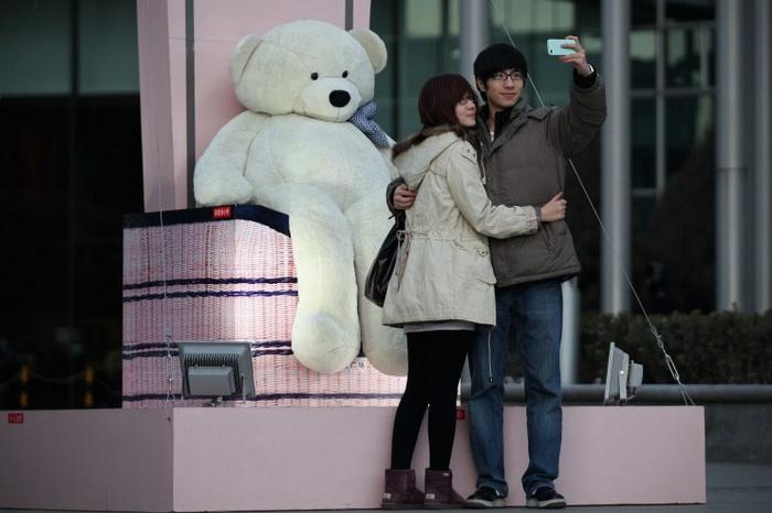 Китаец фотографируется со своей подругой, 14 февраля 2012 года, Пекин, Китай. Треть мужчин в Китае относятся к «остаткам». Фото Feng Li/Getty Images