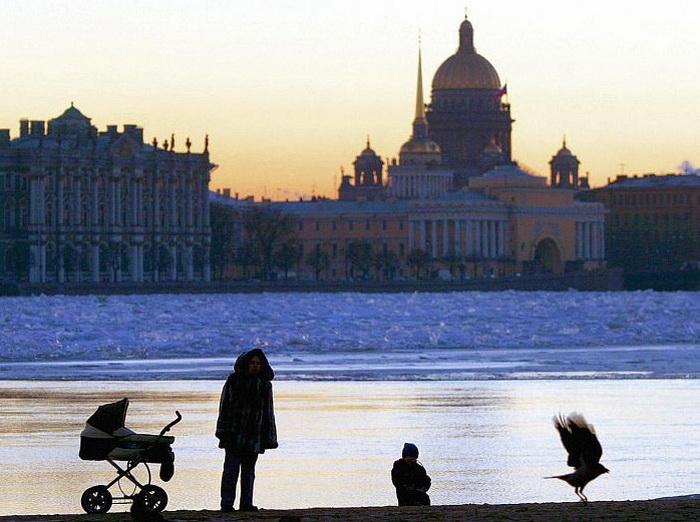 Женщина с ребёнком прогуливается по берегу Невы в Санкт-Петербурге, 14 декабря 2004 года. Санкт-Петербург является городом, который имеет высокий уровень секс-туризма, в частности связанного с эксплуатацией детей. Фото: Сергей Куликов/AFP/Getty Images