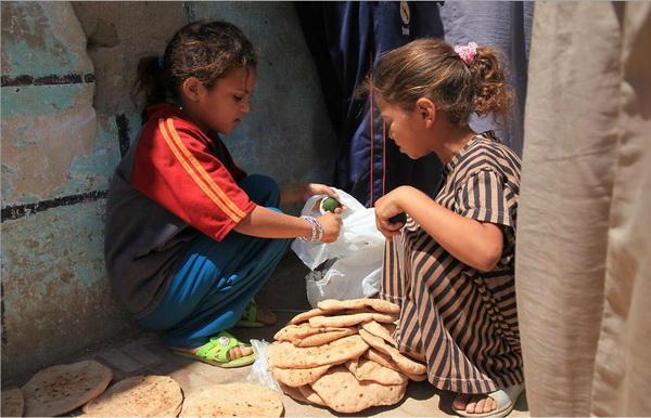 Местные девочки в оазисе Эль Бахарая положили остужать на землю только что купленный хлеб. Фото: Яйра Ясмин/Великая Эпоха