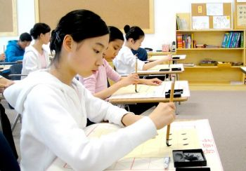 Написание китайских иероглифов традиционным способом с помощью кисточки для некоторых - новый опыт, особенно для китайцев, родившихся в Америке, которые не учились писать по-китайски. Фото: Fei Tian Academy of the Arts California