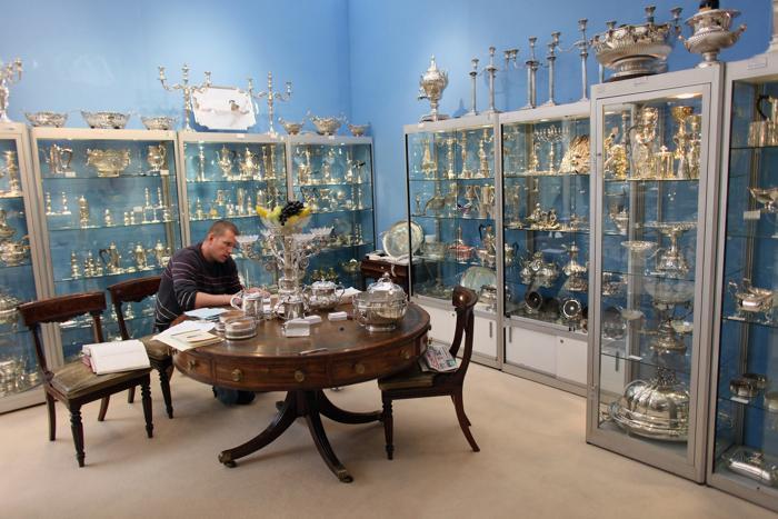 Тони Армстронг смотриткаталог столового серебро стенда Paul Bennett в преддверии выставки изобразительного искусства и антиквариата 2013. Фото: Dan Kitwood/Getty Images