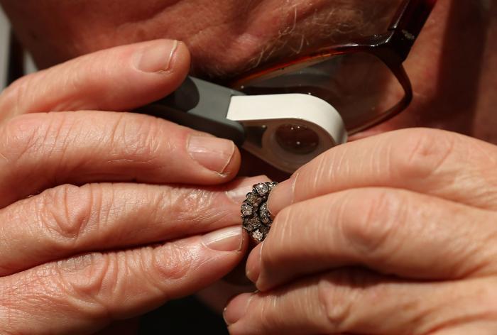 Специалист рассматривает старинные русские серьги в преддверии выставки изобразительного искусства и антиквариата 2013. Фото: Dan Kitwood/Getty Images