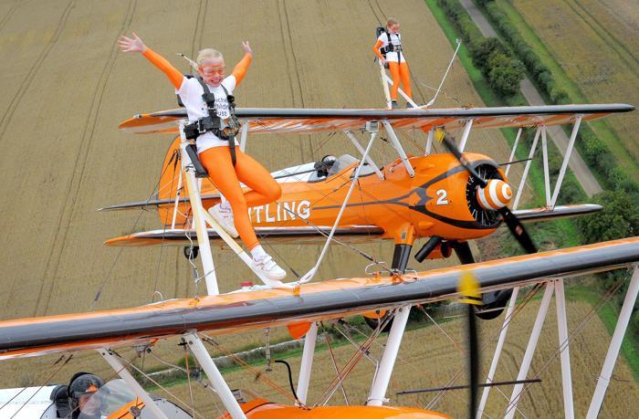 Две 9-летние девочки, сёстры Роза и Флэйм Бревер, совершили полёт на крыльях бипланов 21 августа 2013 года в английском графстве Глостершир, став самой молодой командой в мире по исполнению такого трюка. Фото: Tim Ireland - Pool /Getty Images