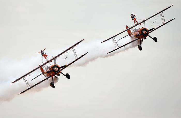 Две 9-летние девочки, сёстры Роза и Флэйм Бревер, совершили полёт на крыльях бипланов 21 августа 2013 года в английском графстве Глостершир, став самой молодой командой в мире по исполнению такого трюка. Фото: Matt Cardy/Getty Images
